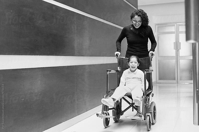 Happy young girl in a wheelchair with mom in a hospital by Per Swantesson for Stocksy United