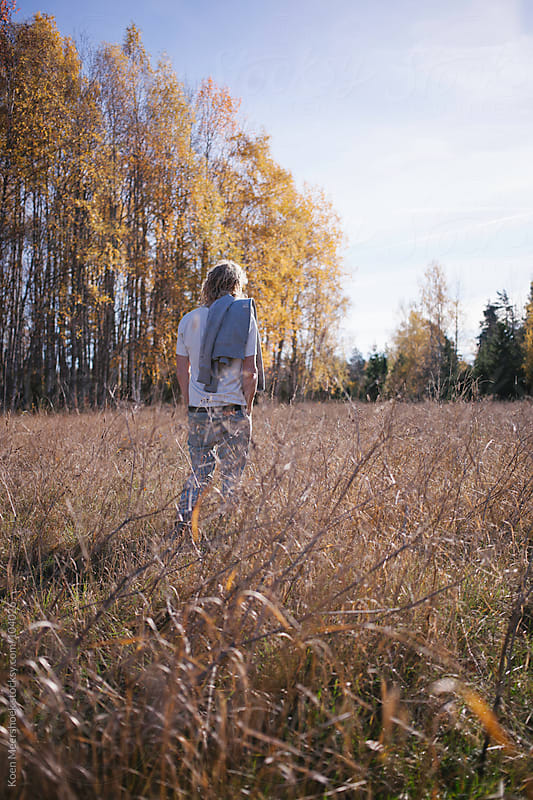 Man walking through high grass on a nice autumn day by Koen Meershoek for Stocksy United