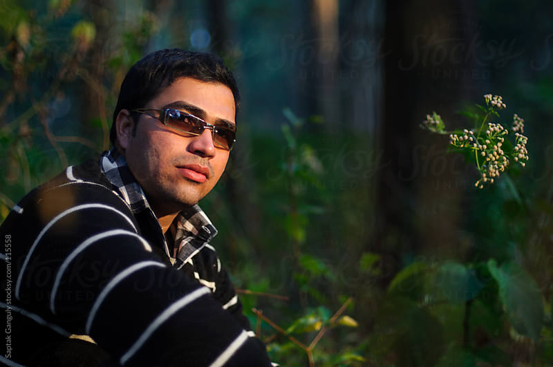 Outdoor portrait of young man in forest by Saptak Ganguly for Stocksy United