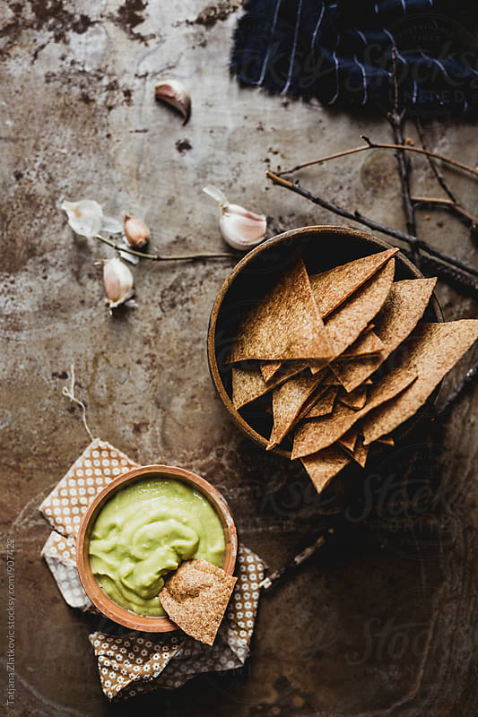 Homemade guacamole and nacho chips by Tatjana Ristanic for Stocksy United
