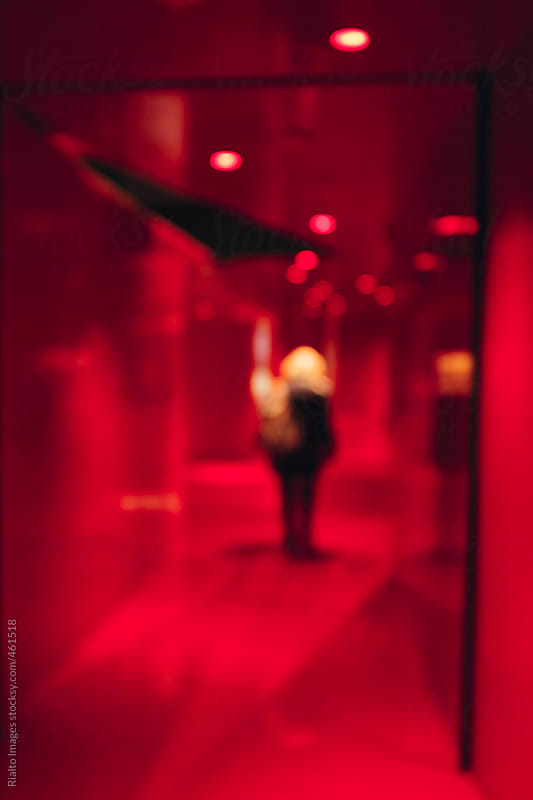 Woman walking down red hallway, blurred focus by Paul Edmondson for Stocksy United