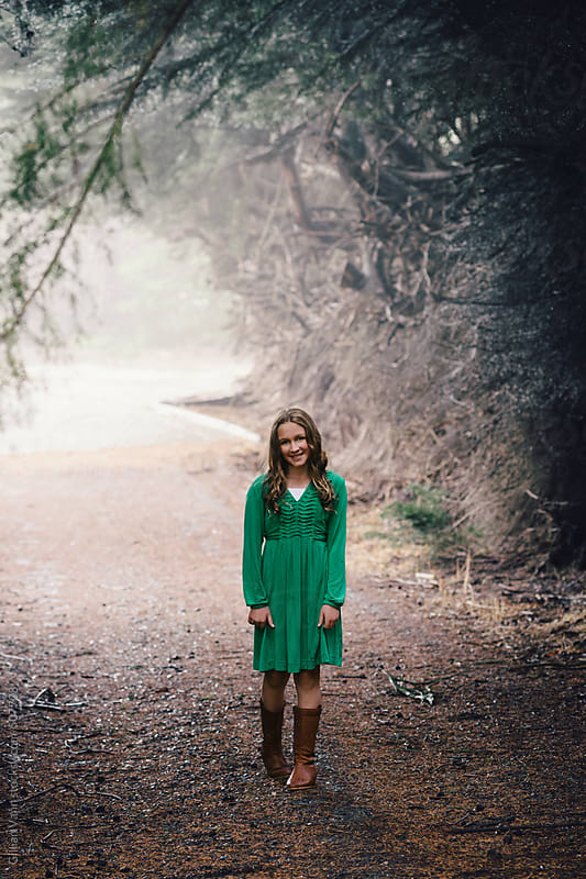 girl in the woods in a green dress walking up a driveway, smiling by Gillian Vann for Stocksy United
