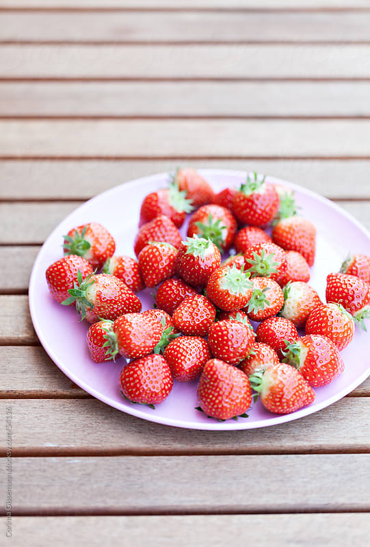 a group of fresh red juicy strawberries on a plate on wooden table by Corinna Gissemann for Stocksy United