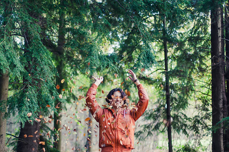 Teenage boy in orange jacket throwing autumn leaves over his head by Cindy Prins for Stocksy United