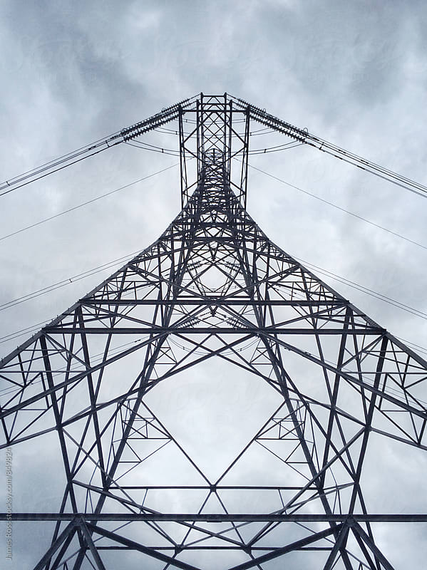 An electricity pylon against blue sky by James Ross for Stocksy United