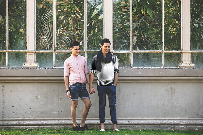 Smiling gay couple holding hands in front a greenhouse.  by BONNINSTUDIO for Stocksy United