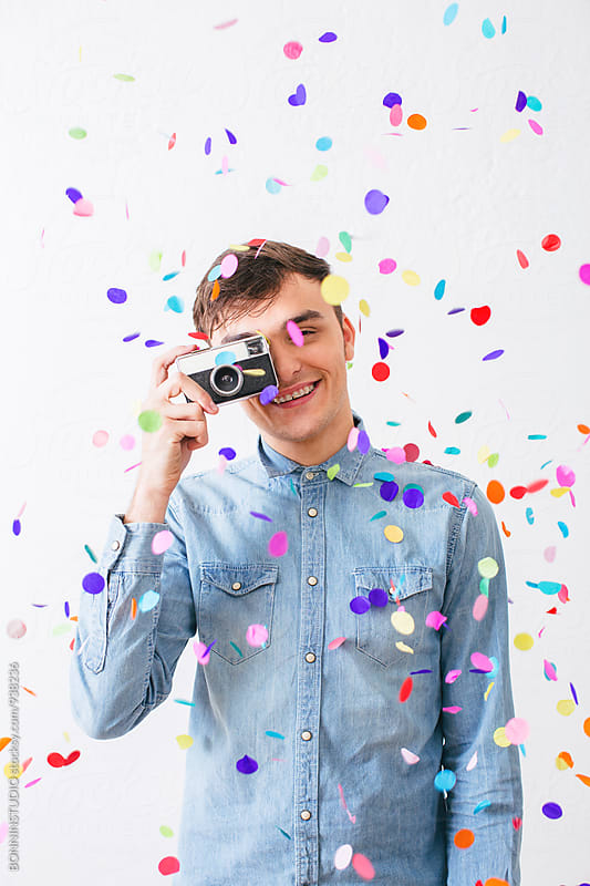 Smiling man taking a photo with an old camera as confetti falls from above. by BONNINSTUDIO for Stocksy United