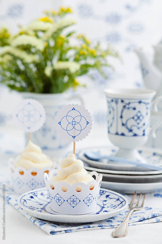 Coffee table with cupcakes with cream cheese frosting and toppers with indian blue porcelain by Elisabeth Coelfen for Stocksy United