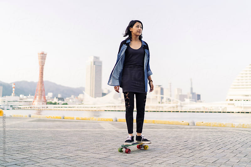 attractive young asian woman skating in Kobe Japan by Juri Pozzi for Stocksy United