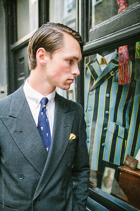 Young man looking in a shop window at mens clothing by kkgas for Stocksy United