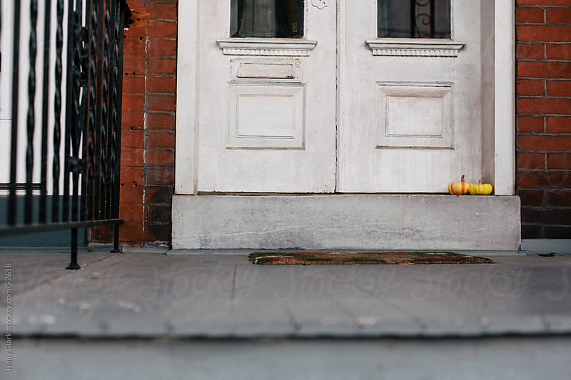Two small pumpkins sit on a city front porch. by Holly Clark for Stocksy United