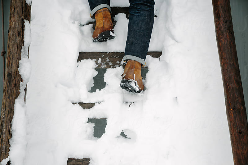 Man Climbing Steps Covered In Deep Snow by Luke Mattson for Stocksy United