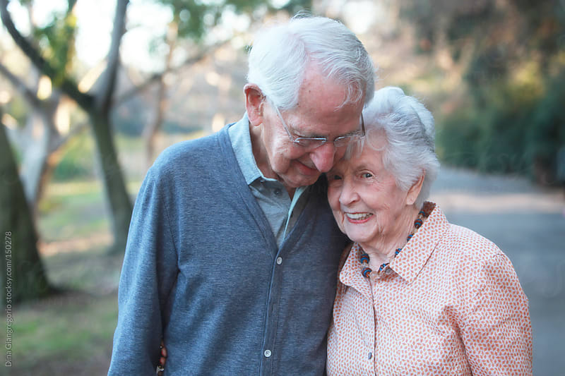 Senior couple hugging in park by Dina Giangregorio for Stocksy United