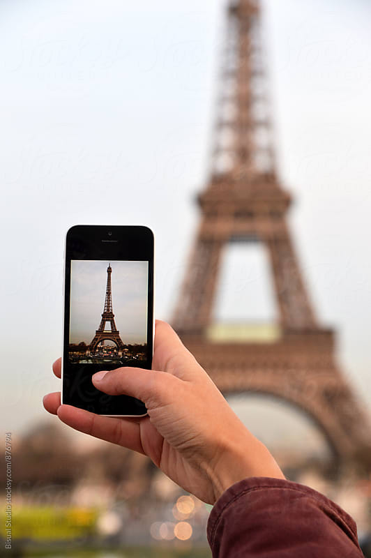 Woman taking photos with a smartphone to the Eiffel Tower by Bisual Studio for Stocksy United