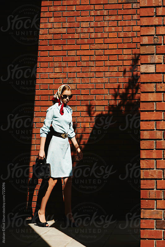 Blonde girl posing against brick walls by Atakan-Erkut Uzun for Stocksy United
