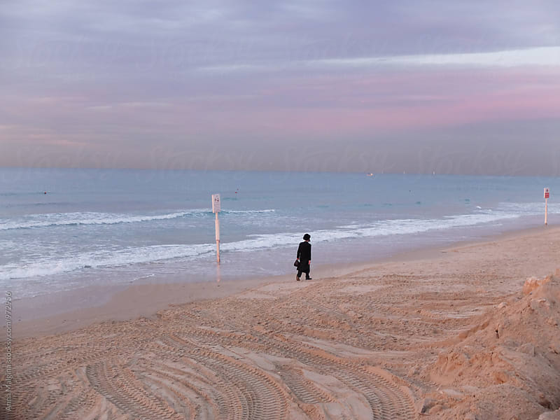 An anonymous jewish orthodox man on beach in Tel-Aviv  by Anna Malgina for Stocksy United
