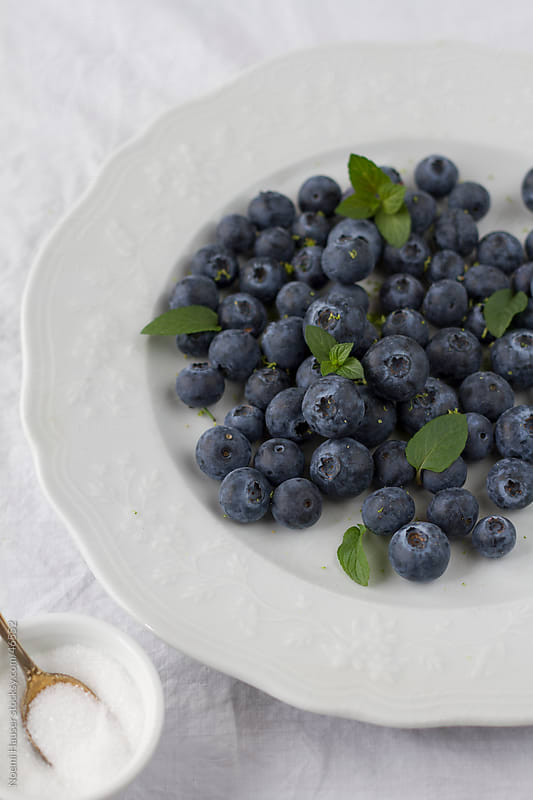 Blueberries with sugar and mint leaves by Noemi Hauser for Stocksy United