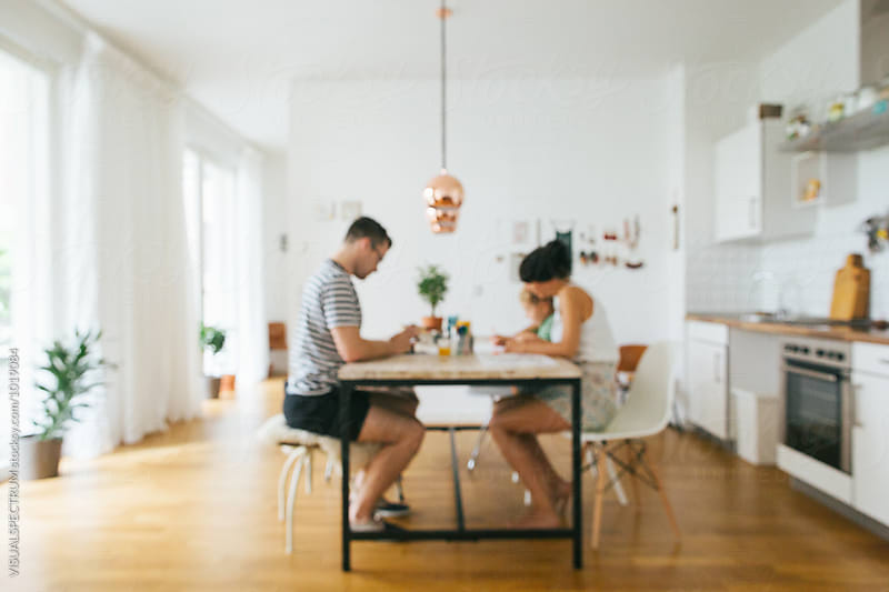 Defocused shot of Young Parents Painting With Small Blond Boy in Bright Living Room Defocused by Julien L. Balmer for Stocksy United