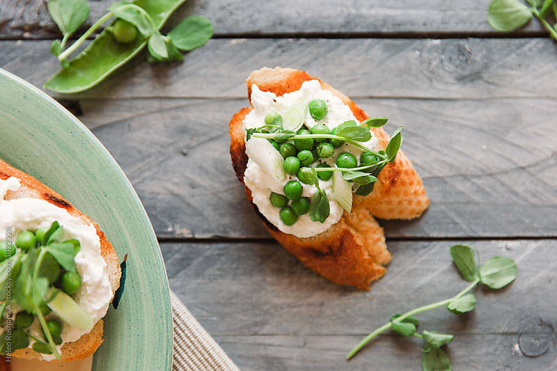 Crostini with spring vegetables and ricotta. by Helen Rushbrook for Stocksy United