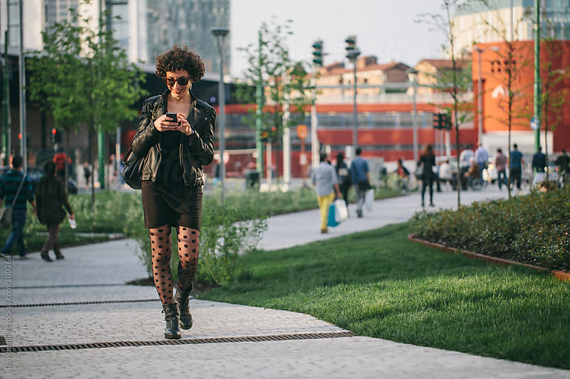Young woman on the phone walking in the business district by Davide Illini for Stocksy United