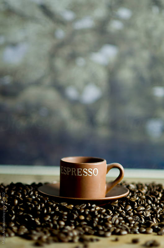 Spilled coffee beans with cup of espresso coffee by Marija Anicic for Stocksy United