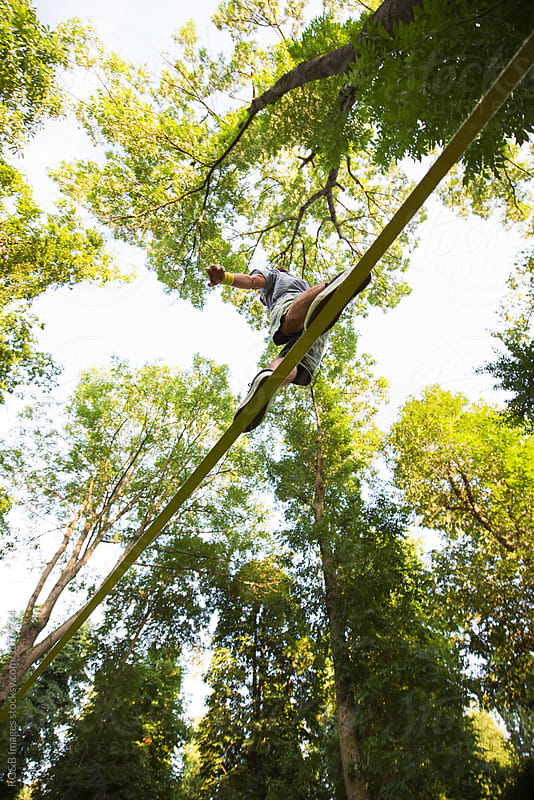 Man walking along a tightrope highline between the trees by RG&B Images for Stocksy United