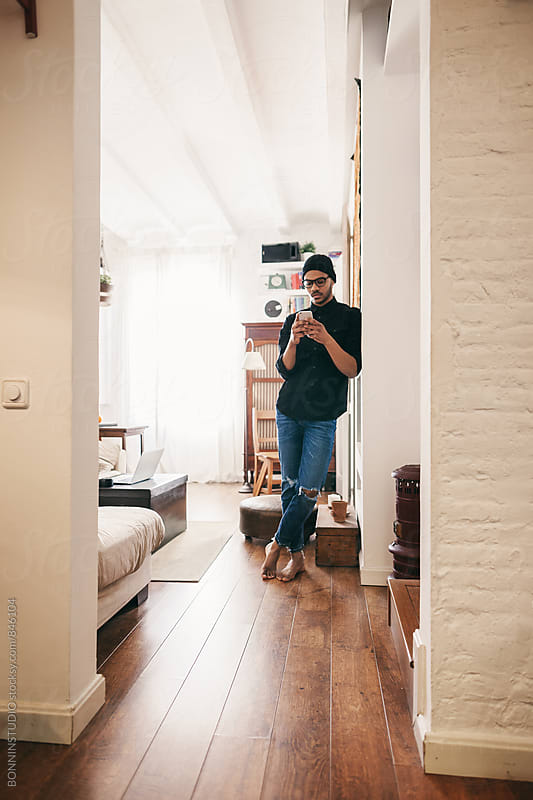 Latin man standing using phone at home. by BONNINSTUDIO for Stocksy United