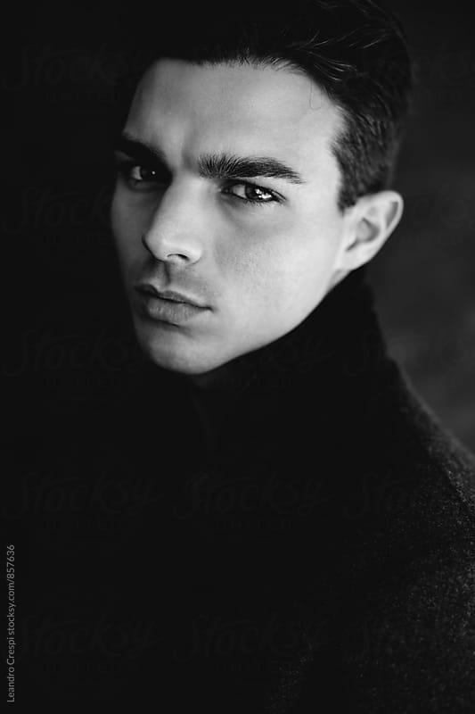 Closeup portrait of a young male in black and white by Leandro Crespi for Stocksy United
