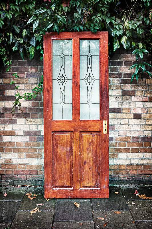 A front door by a brick wall by James Ross for Stocksy United