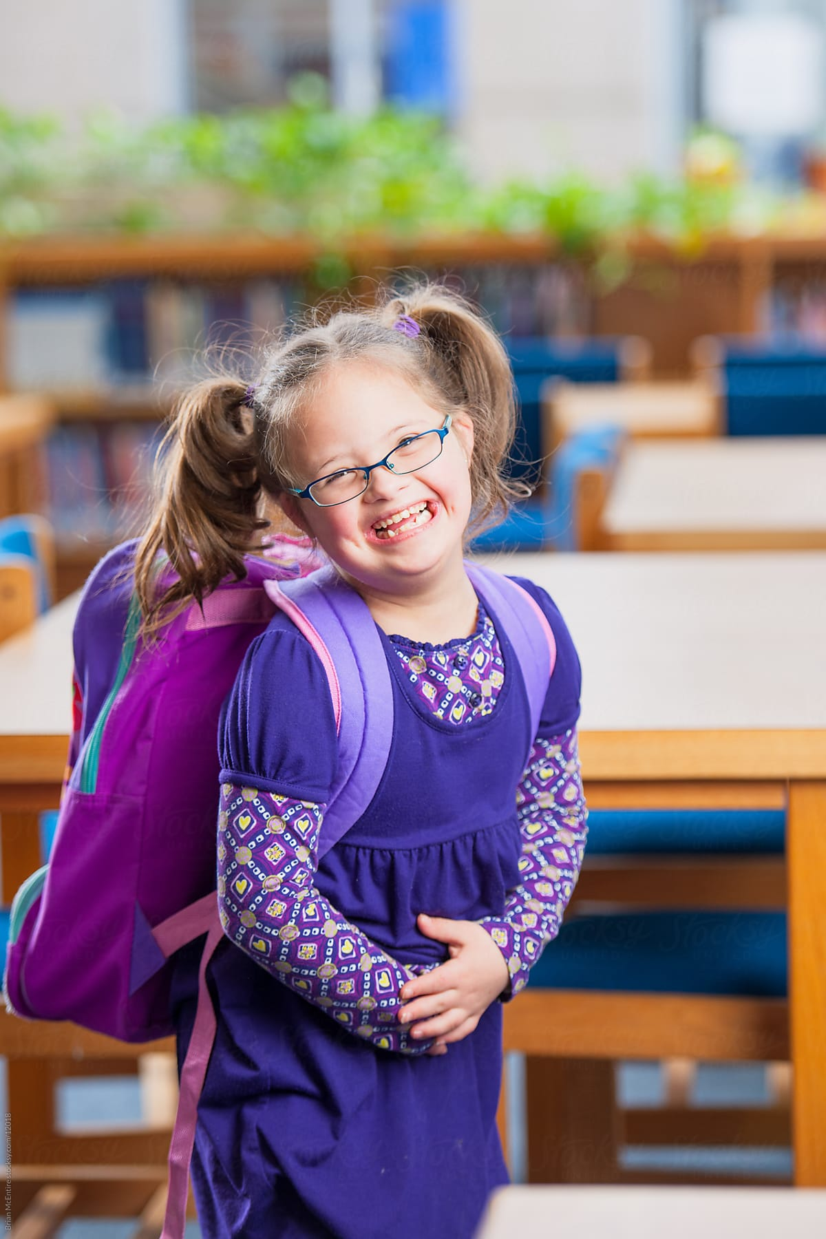 Giggly Second Grade Girl With Down Syndrome In School Library by Brian McEntire