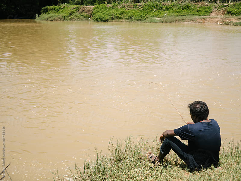 Indian fisherman fishing in dirty river by Martin Matej for Stocksy United