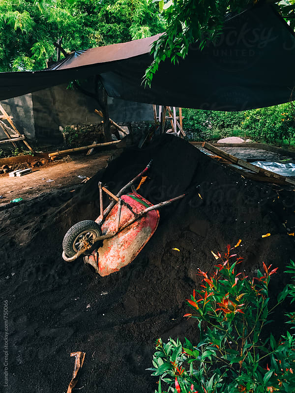 A wheelbarrow up side down over a dirt mound by Leandro Crespi for Stocksy United