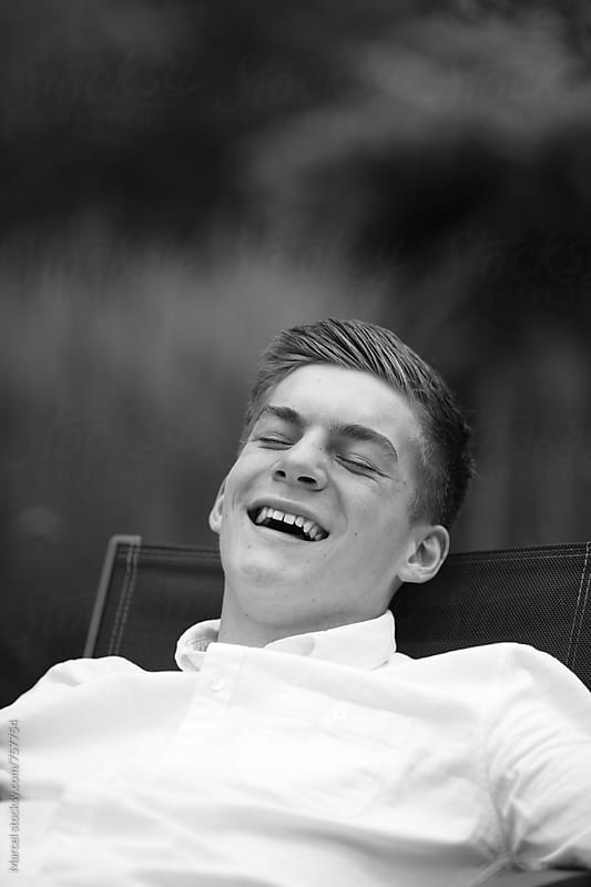 Young man laughing real hard by Marcel for Stocksy United