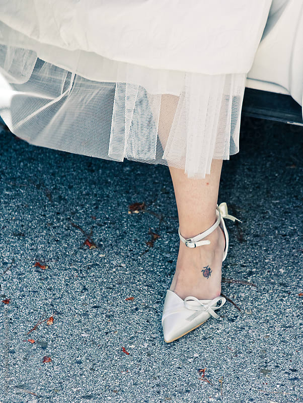 Bride stepping out of limo, focus on lower part of her dress and shoe by Monica Murphy for Stocksy United