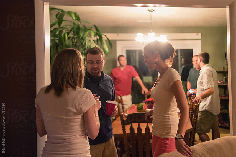 House Party: Guests Talk In Dining Room by Brian McEntire for Stocksy United