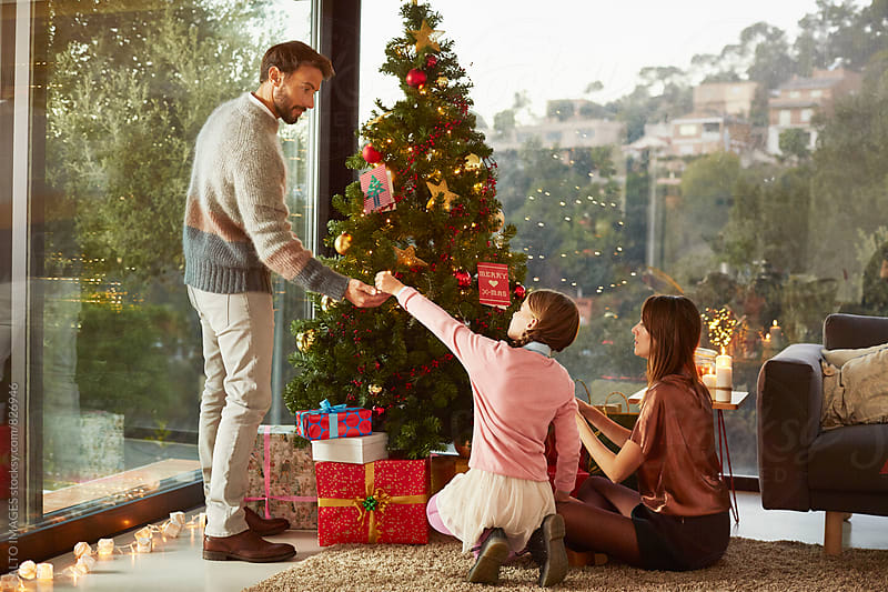 Family Decorating Christmas Tree At Home by ALTO IMAGES for Stocksy United