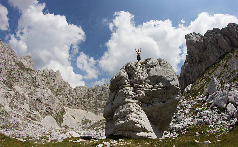 Climber raising hands on the top of the rock in the mountains by Marko Milovanović for Stocksy United
