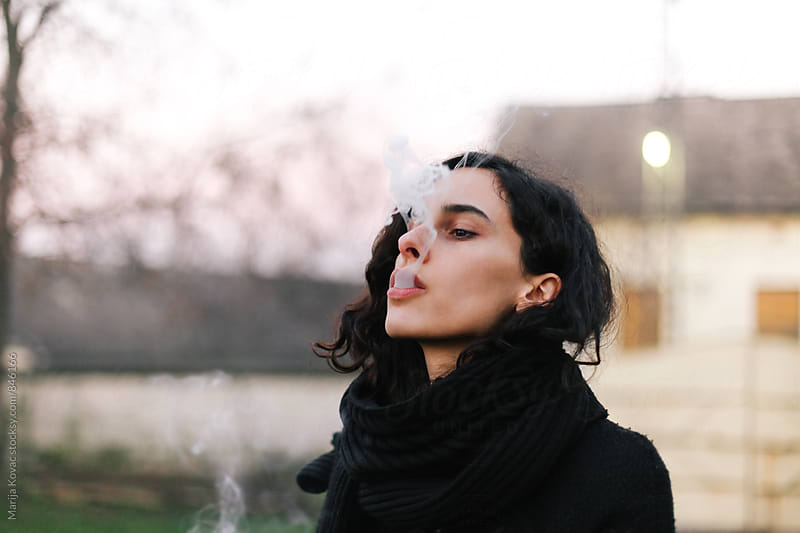 Beautiful woman blowing a cigarette smoke outdoor  by Marija Kovac for Stocksy United
