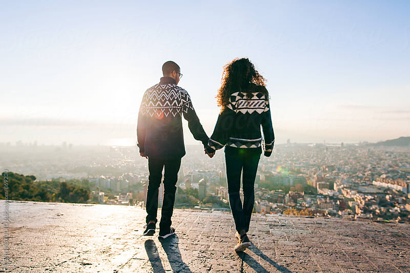 Back view of young couple holding hands above Barcelona. by BONNINSTUDIO for Stocksy United