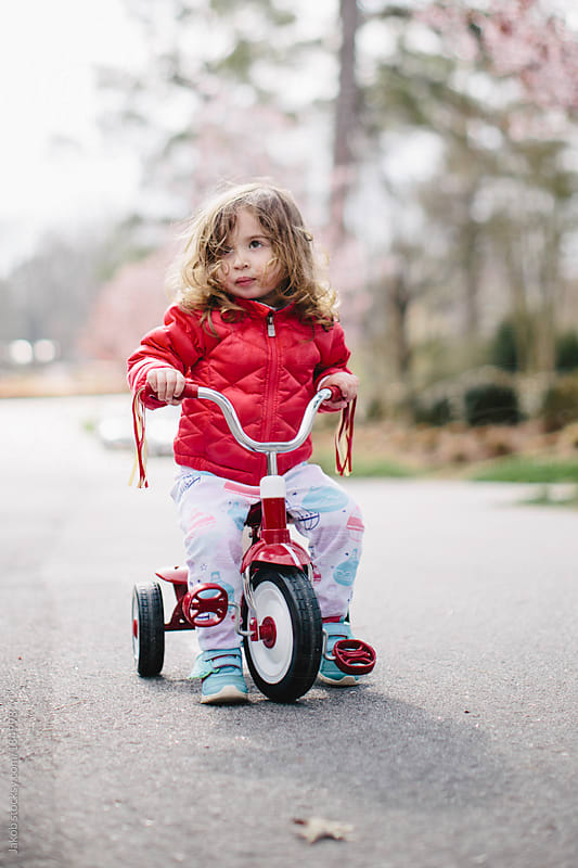 Toddler sitting on a tricycle by Jakob for Stocksy United