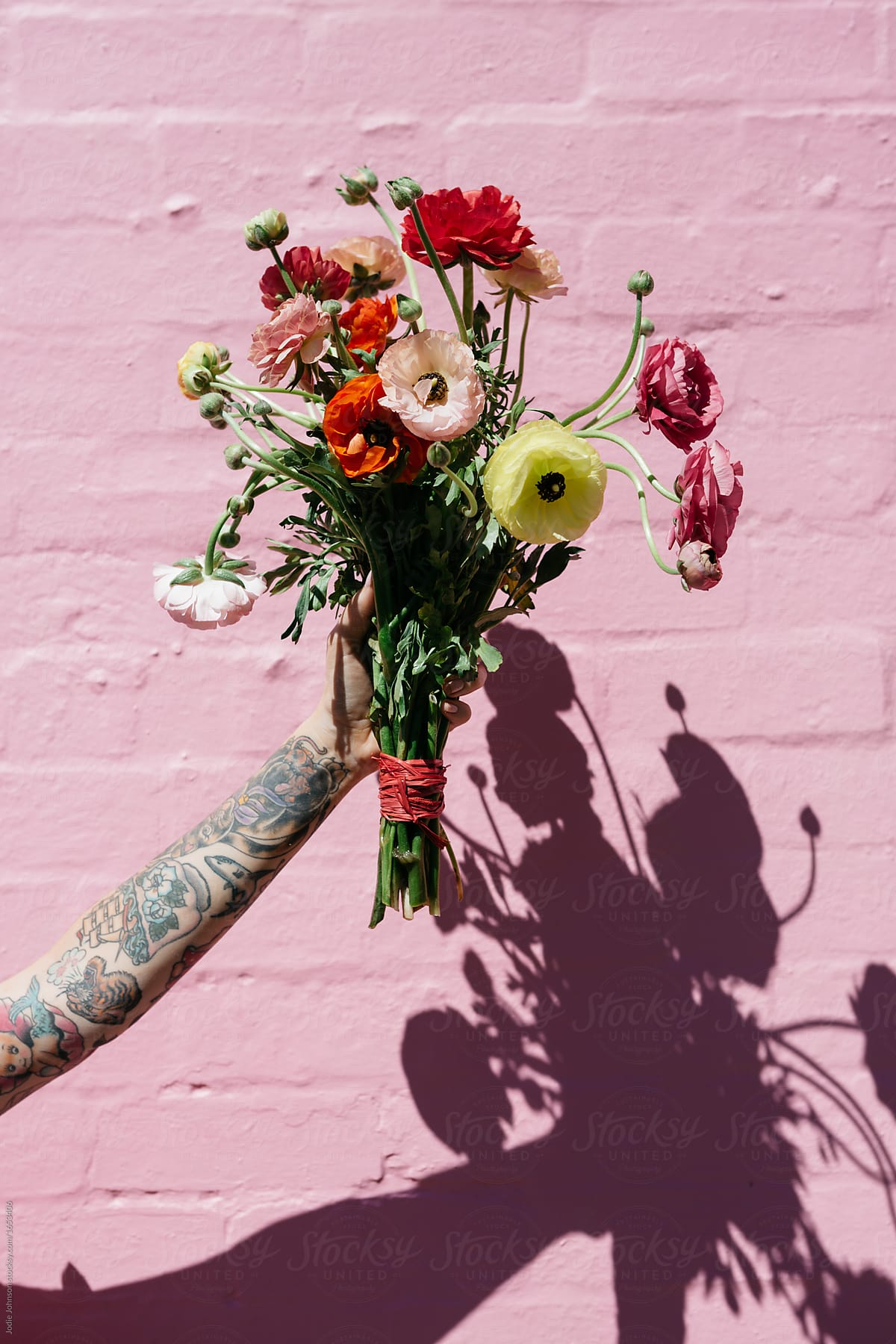 Female Arm With A Sleeve Tattoo Holding A Bunch Of Colorful Flowers