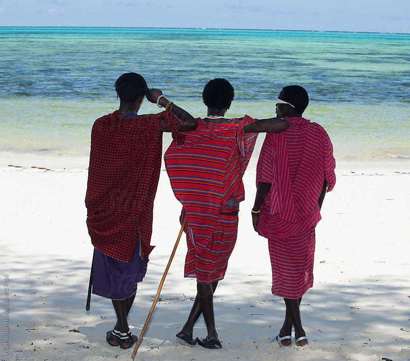 Maasai tribesmen on Zanzibar beach. Tanzania by Hugh Sitton for Stocksy United