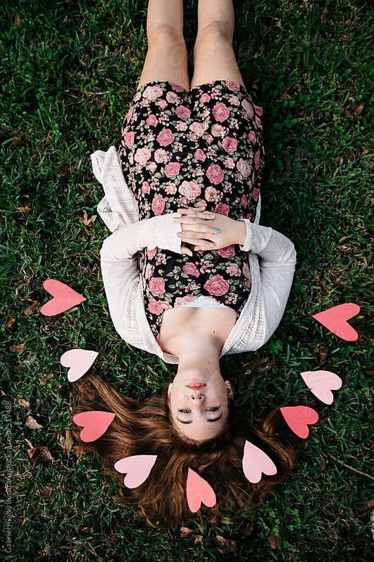 Girl laying on the grass with pink hearts around her by Gabriel (Gabi) Bucataru for Stocksy United