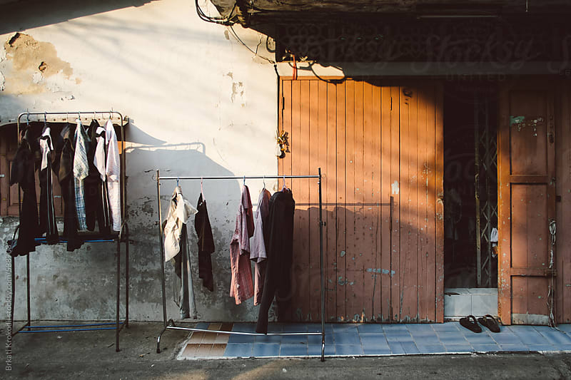 Clothes hanging in front of an old house in Bangkok by Brkati Krokodil for Stocksy United