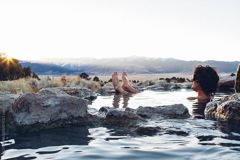 Man Relaxes in Natural Hot Spring with Mountain View and Snow by MEGHAN PINSONNEAULT for Stocksy United