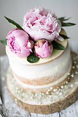 Naked Wedding Cake Decorated With Fresh Flowers Stocksy United