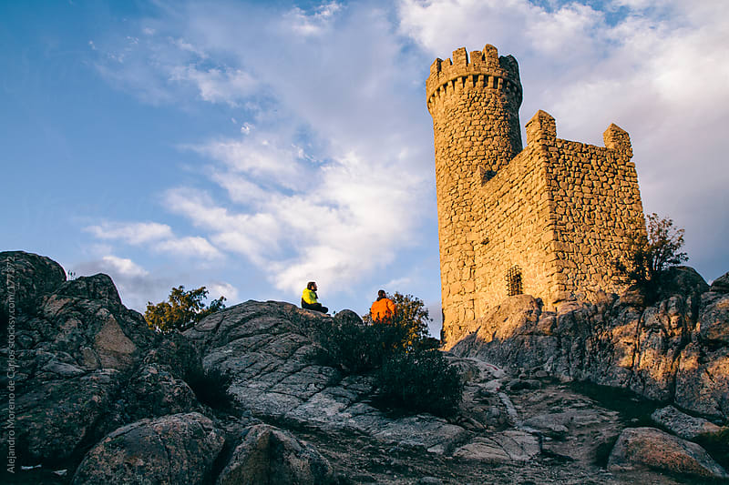 Castle medieval tower at sunset and two young men by Alejandro Moreno de Carlos for Stocksy United