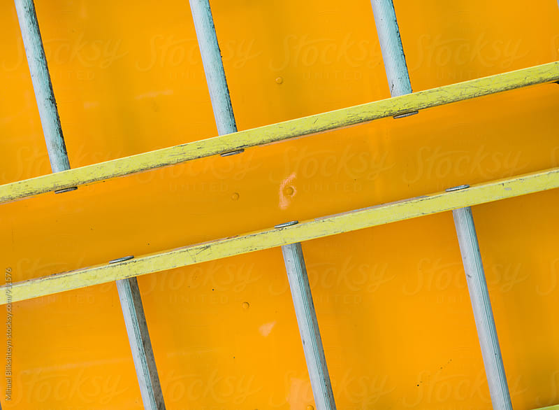 Closeup of yellow ladders on the side of a yellow truck by Mihael Blikshteyn for Stocksy United