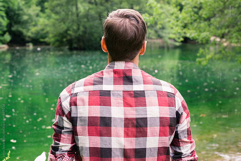 Back shot of a man wearing a checkered shit looking out onto a green lake at a park by Jovo Jovanovic for Stocksy United