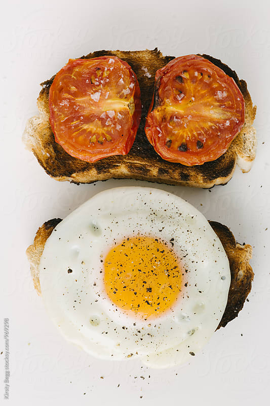 Grilled tomatoes on toast with a fried egg on toast by Kirsty Begg for Stocksy United